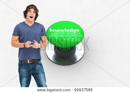 The word knowledge and open-mouthed student holding a cellphone against digitally generated green push button