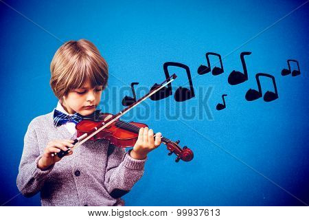 cute little boy playing violin against blue background