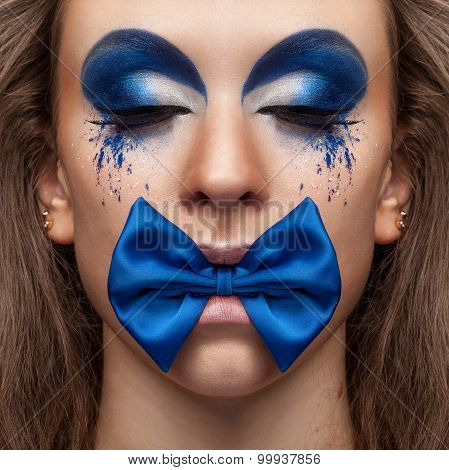 Beautiful Model With Blue Make Up And Bow In Mouth