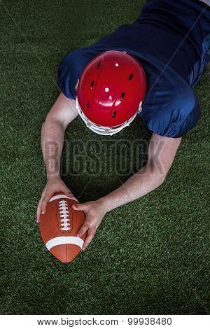 Upward view of an american football player scoring a touchdown