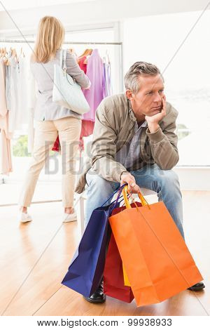 Bored man waiting for his shopping woman in clothing store