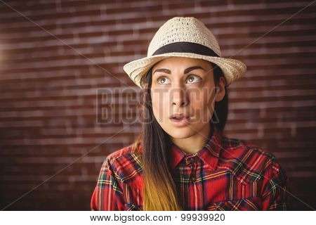 Beautiful hipster looking confused on red brick background