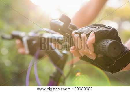 Woman mountain biking and holding handlebars in the nature