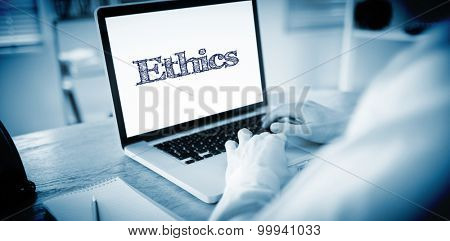 The word ethics against businessman working on his laptop