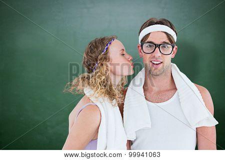 Geeky hipster kissing her boyfriend against green chalkboard