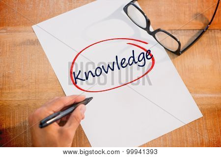The word knowledge against left hand writing on white page on working desk