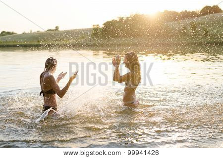 Two amazing young females having fun in lake slushing water