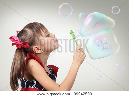 Portrait Of Child Girl Blowing Soap Bubble Forming House, Habitation Concept