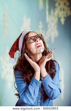 Beautiful teenage girl wearing Santa hat and glasses looking up