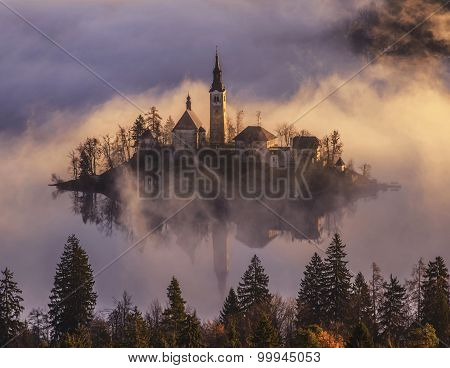 Mystical Sunrise Over Lake In The Mountains. Mist Is Over The Lake Covering The Church