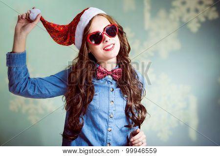 Funny brunette girl in Christmas hat and heart-shaped glasses