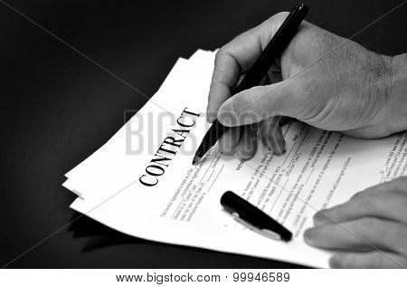 Contract on desk with black pen being signed by person