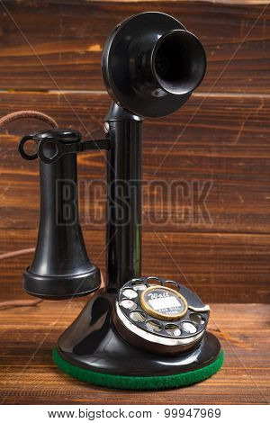 A vintage, old-fashioned, antique candlestick telephone on a wood background