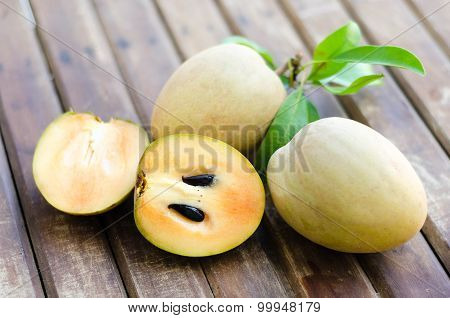 Fresh Sweet Sapodilla Fruit With Leaves On Wooden Background