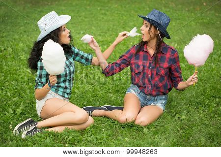 beautiful girls in cowboy hats eating cotton candy