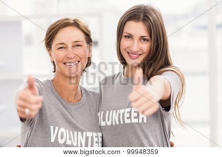 Portrait of smiling female volunteers doing thumbs up in the office