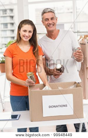 Portrait of smiling casual business colleagues sorting donations in the office