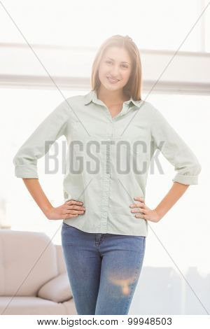 Portrait of smiling casual businesswoman with hands on hips in the office
