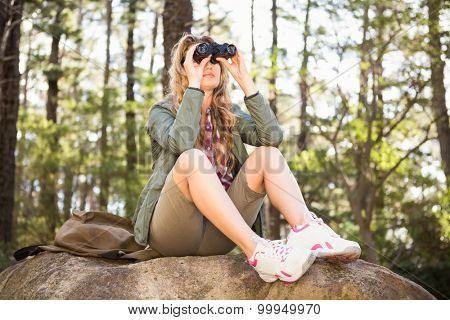 Blonde hiker looking through binoculars and sitting on stone in the nature