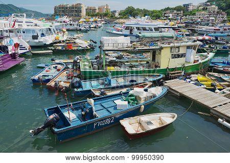 Man fixes fishing boat at Sing Kee harbor in Hong Kong, China.