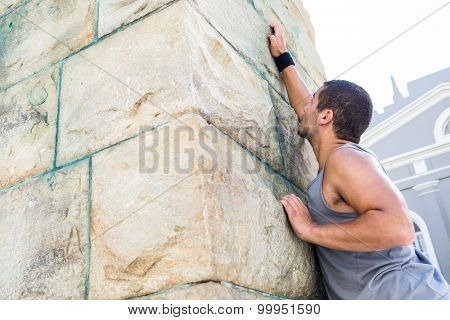 Extreme athlete gripping to wall in the city