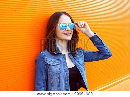 Portrait Of Beautiful Young Smiling Woman Wearing A Sunglasses And Jeans Jacket In The City