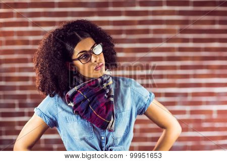 Attractive hipster posing with hands on hips against red brick background