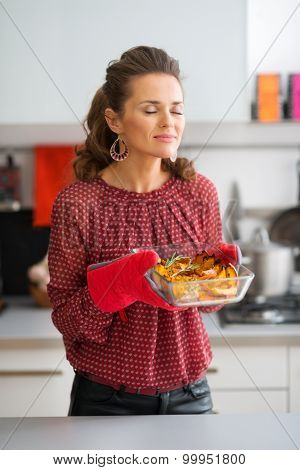 Woman Cook In Kitchen Enjoying The Smell Of Roasted Pumpkin