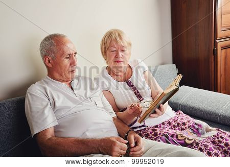 Older Man And Woman 60-65 Years Old Sitting On The Sofa And Reading A Book