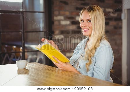 Portrait of smiling blonde turning the page of yellow book at coffe shop