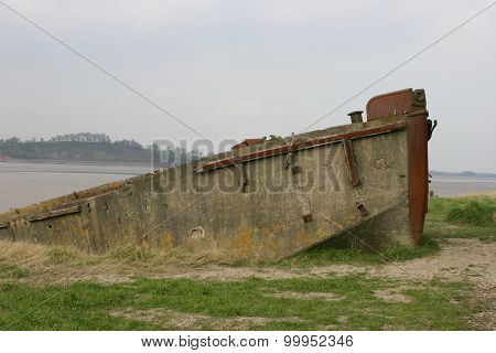 Decaying concrete barge hulk on river bank