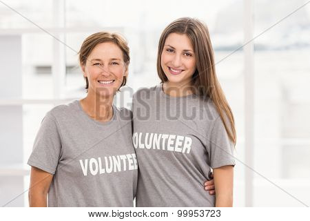 Portrait of smiling female volunteers putting arms around each other in the office