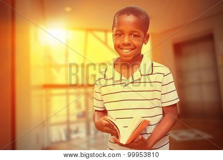 happy pupil with book against foyer area with elevator