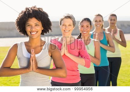 Portrait of smiling sporty women doing prayer position in yoga class in parkland