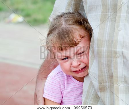 little girl sheds tears protected parent