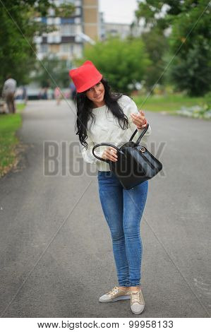 girl in a red hat with ears, holding a bag on the street