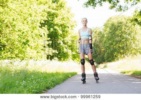 fitness, sport, summer and healthy lifestyle concept - happy young woman in roller skates and protective gear riding outdoors