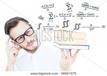 Geeky young man looking at pile of books against maths equation