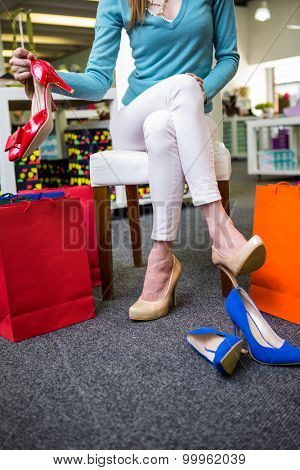 Woman trying on different shoes in fashion boutique