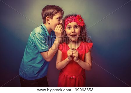 Teen boy whispering in the ear of teen girl on a gray  backgroun