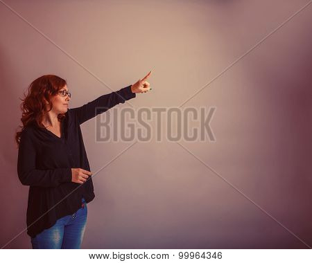 European - looking  woman  of  30  years  is pointing in the  di