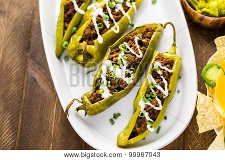 Chipotle beef & bean stuffed chile peppers garnished with sour cream and scallions.
