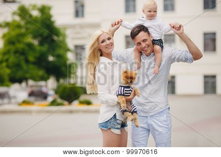 Mother, father, little boy and dog having fun in the green park.