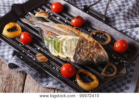 Grilled Dorado Fish With Vegetables Close Up On A Grill Pan On The Table.