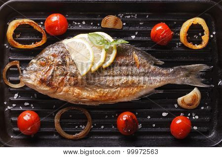 Dorado Fish With Vegetables Closeup On The Grill. Horizontal Top View