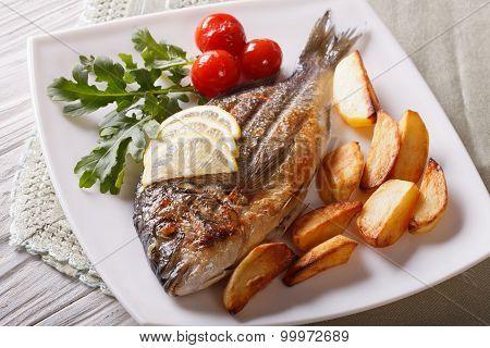 Dorado Fish With Fried Potatoes And Lemon Closeup. Horizontal