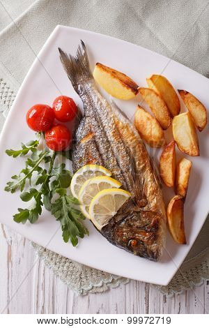 Grilled Dorado Fish With Fried Potatoes Close-up. Vertical Top View