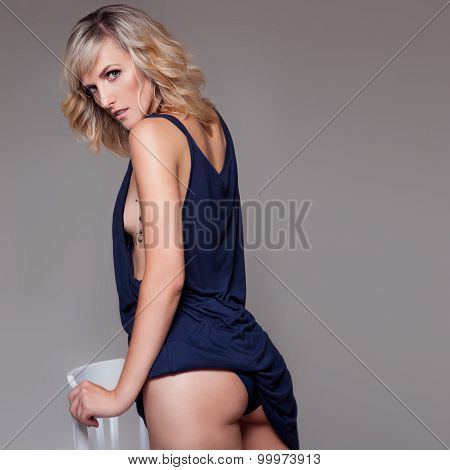 beautiful sexy woman in a blue shirt  looks out from under the shirt pretty round sexy ass tattoo
