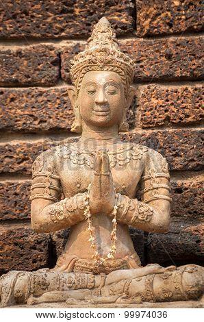 Stone buddha statue seated in prayer pose at Wat Jet Yod, Chiang Mai, Thailand