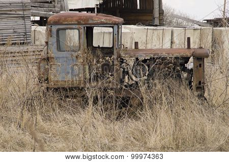 Remains of an ancient tractor on caterpillar to a course in a grass